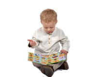 Baby sitting cross-legged reading a book Stock Photos