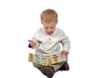 Baby sitting cross-legged reading a book Stock Photos