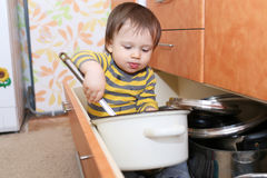 Baby sitting in drawer on kitchen Royalty Free Stock Photo