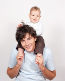 Baby sitting on father neck on white Stock Images