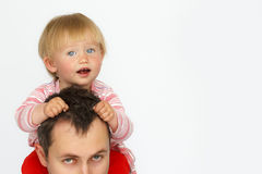 Baby sitting on father neck on white background stock images