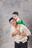 Baby sitting on father neck on white background in studio. Baby sitting on father neck on white background Royalty Free Stock Photo
