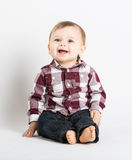 Baby Sitting in Flannel and Jeans Looking Above Camera Royalty Free Stock Photography
