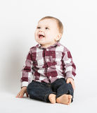 Baby Sitting in Flannel and Jeans Looking Left Laugh Stock Photography