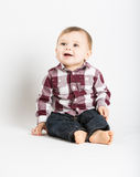 Baby Sitting in Flannel and Jeans Looking Up and Left. A cute 1 year old baby sits in white studio with jeans and a red white flannel looking and laughing Royalty Free Stock Photos
