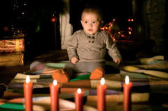 Baby sitting on  floor near fireplace. On Christmas Eve Royalty Free Stock Images