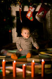 Baby sitting on  floor near fireplace. On Christmas Eve Stock Photo