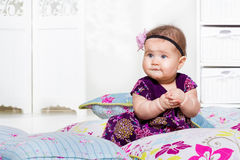 Baby sitting among pillows Stock Image