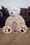 Baby sitting in front of giant teddy bear Stock Photos