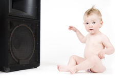 Baby sitting in front of loudspeaker Royalty Free Stock Photography