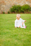 Baby sitting on grass Stock Image