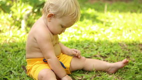 Baby sitting on the grass and digging in the ground stock footage