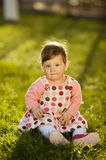 Baby sitting on grass in garden Stock Images