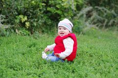 Baby sitting on grass outdoors. Baby age of 11 months in red waistcoat sitting on grass outdoors Stock Images