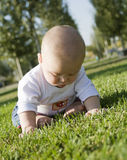 Baby sitting on grass playing. Barefoot blonde baby sitting on the grass playing Stock Images
