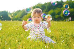 Baby sitting on the grass. Stock Photos