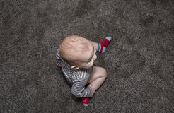 Baby sitting on gray carpet. Stock Photo