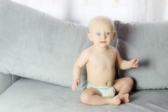 Baby sitting on a gray sofa in the living room Stock Image