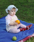 Baby sitting on green lawn Stock Photo
