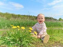 Baby sitting on a green meadow with yellow flowers dandelions Stock Photo