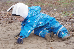 Baby sitting on ground outdoors Stock Photo