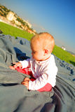 Baby is sitting on the ground outside Royalty Free Stock Photo