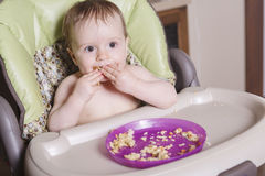 Baby sitting in high-chair eating with her hand Stock Images