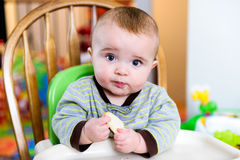 Baby Sitting in a High Chair Eating a Snack. A baby sits in a highchair eating a snack Stock Image