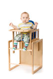 Baby sitting in highchair. Baby sitting in highchair  isolated on white Royalty Free Stock Images