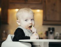 Baby Sitting in Highchair All Messy Eating Orange Baby Food with. Baby Sitting in Highchair All Messy Eating Orange Carrot Baby Food with Spoon in Mouth Royalty Free Stock Images