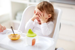 Baby sitting in highchair and eating at home. Food, child, feeding and people concept - baby with spoon sitting in highchair and eating puree from at home Royalty Free Stock Photo