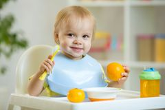 Baby sitting in highchair and eats oranges Royalty Free Stock Photo