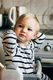 Baby sitting in highchair. Kid sits at empty table and wait for your feeding. He is blonde cute toddler in tabby wear Stock Photography