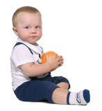 Baby sitting and holding an orange stock image