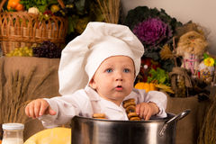 Baby sitting inside a large cooking stock pot. Portrait of a baby wearing a chef hat sitting inside a large cooking stock pot surrounded by vegetables and food Royalty Free Stock Image