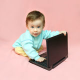 Baby sitting with laptop Stock Photography