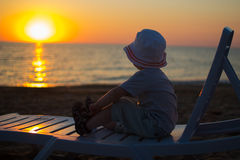 Baby sitting on a lounger  and enjoy the sunset Stock Image