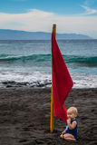 Baby sitting near red flag on Playa la Arena black volcanic sand beach. Tenerife, Canary islands Royalty Free Stock Images