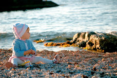 A baby sitting near the sea. A baby sitting and playing near the sea royalty free stock photo