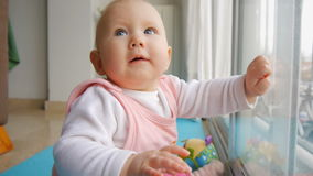 Baby sitting near window observing camera and tries to catch it. stock footage