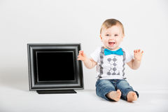 Baby Sitting Next to Picture Frame and Excited. A cute 1 year old baby sits next to a blank black picture frame in a white studio setting. HThe boy is extremely Stock Images