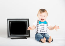 Baby Sitting Next to Picture Frame and Yelling Royalty Free Stock Image