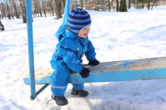 Baby sitting on old seesaw outdoors in winter Stock Photo