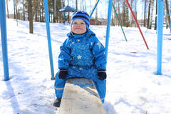 Baby sitting on old seesaw in winter Stock Image