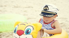 Little Caucasian boy in sailor suit and cap sitting on the beach in swim ring and laughs. Baby sitting om the beach with swim ring Stock Images