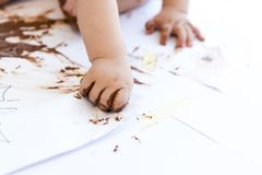 Baby painting with hands with chocolate Stock Photo