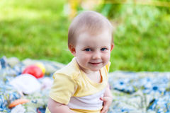 A baby is sitting on plaid on the field Stock Image