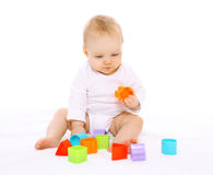 Baby sitting and playing with colorful toys Royalty Free Stock Image