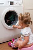 Baby sitting on potty. A young baby sitting on a potty in front of the washing machine royalty free stock photo