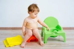Baby sitting on a potty stock photo